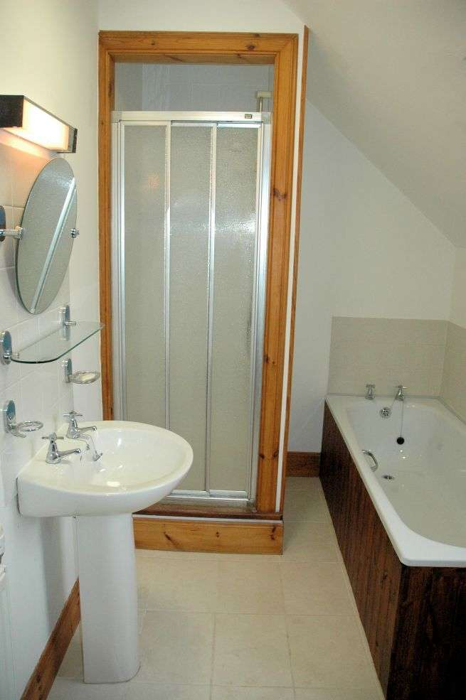 The main family bathroom in Tigharry Cottage is accessed from the rear of the landing. There is both a bath and separate shower cubicle which has a mixer shower.