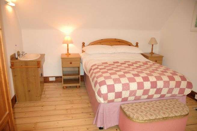 The master bedroom in Tigharry Cottage is to the left off the landing at the top of the stairs. It is at the front of the cottage and has excellent sea and mountain views across Loch Carron.