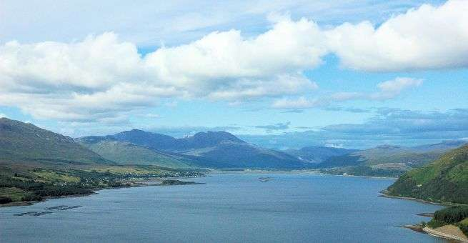 """A panoramic view along the length of Loch Carron. Its namesake, Lochcarron village, stretches along the north shore of the loch and the unmistakable shape of """"Wellington"""" can be seen in the background."""